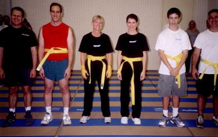 Six people wearing new yellow belts